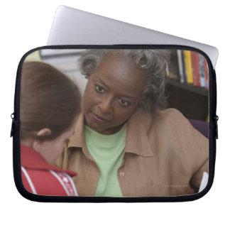 Teacher talking to student laptop sleeve