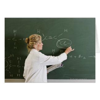 Teacher writing on chalkboard card