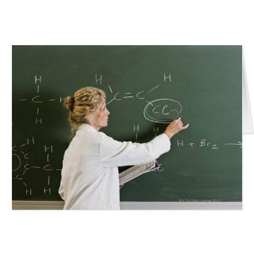 Teacher writing on chalkboard cards