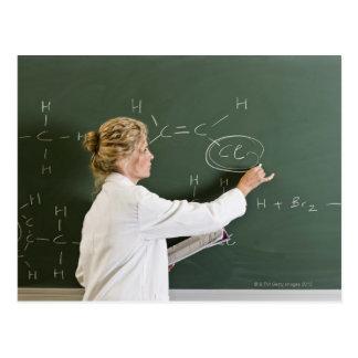 Teacher writing on chalkboard postcard