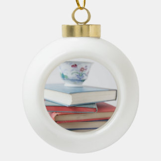 Teacup on book stack ceramic ball christmas ornament