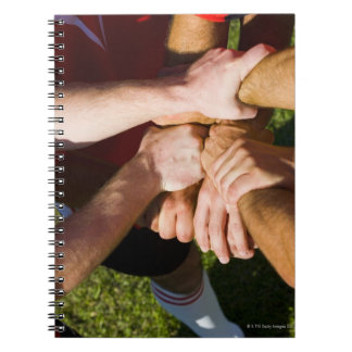 Team with arms-in notebook
