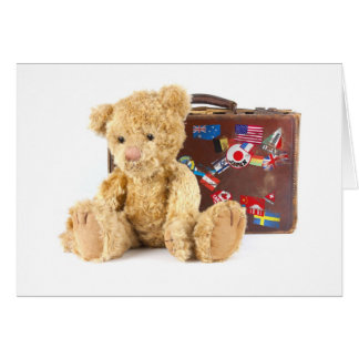 teddy bear and vintage old suitcase with world sti card