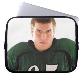 Teen football player holding helmet, portrait laptop sleeve