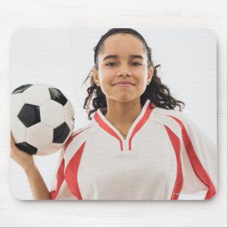 Teen girl holding soccer ball in hand, portrait mouse mat