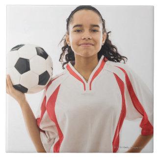Teen girl holding soccer ball in hand, portrait tile