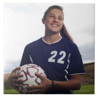 teen girl soccer player holding soccer ball large square tile