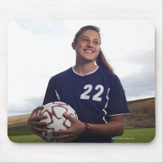 teen girl soccer player holding soccer ball mouse mat