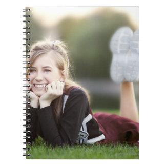 Teen relaxing on grass notebook