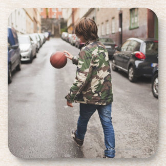 Teenage boy dribbling basketball coaster