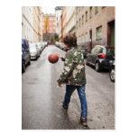 Teenage boy dribbling basketball postcards