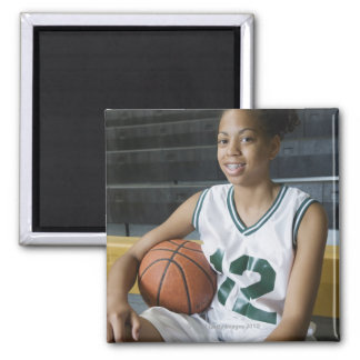 Teenage girl (13-15) wearing basketball uniform, square magnet