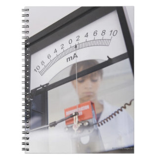 Teenage girl by science equipment notebook