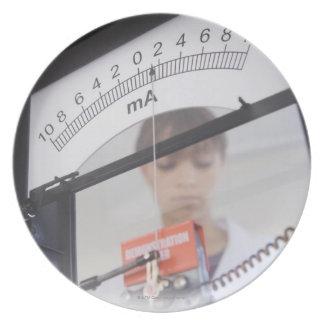 Teenage girl by science equipment plate