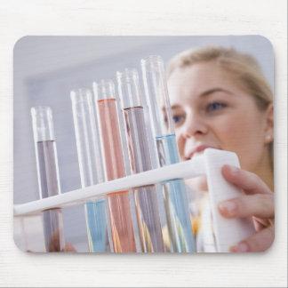 Teenage girl holding rack of test tubes mousepad
