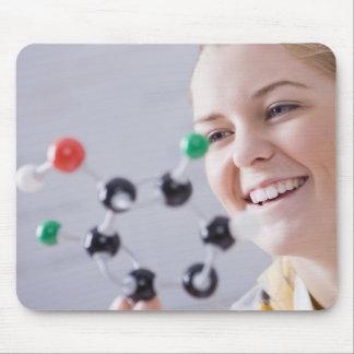 Teenage girl looking at molecule model mouse pads