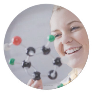 Teenage girl looking at molecule model plate