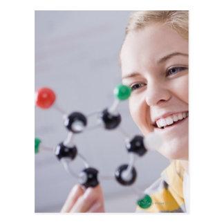 Teenage girl looking at molecule model postcard