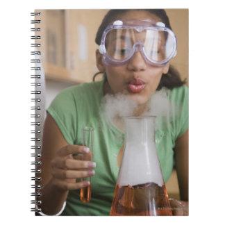 Teenage girl performing science experiment notebook