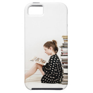 Teenage girl reading comic strip by pile of case for the iPhone 5