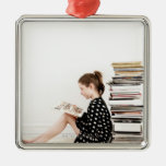 Teenage girl reading comic strip by pile of ornament