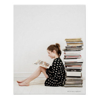 Teenage girl reading comic strip by pile of poster