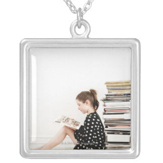 Teenage girl reading comic strip by pile of silver plated necklace