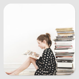 Teenage girl reading comic strip by pile of square sticker