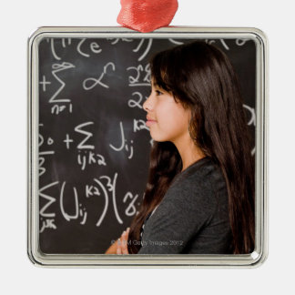 Teenage girl student at blackboard with math christmas ornament