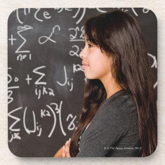Teenage girl student at blackboard with math coaster