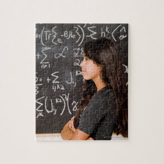 Teenage girl student at blackboard with math jigsaw puzzle