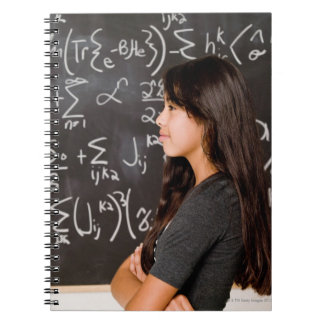 Teenage girl student at blackboard with math notebooks