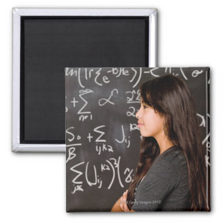 Teenage girl student at blackboard with math square magnet