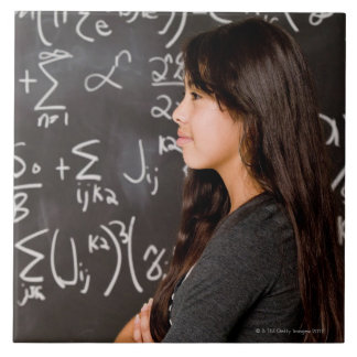 Teenage girl student at blackboard with math tile