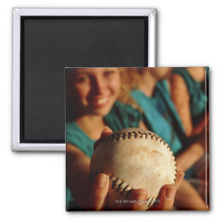 Teenage girls' softball team sitting in dugout magnet