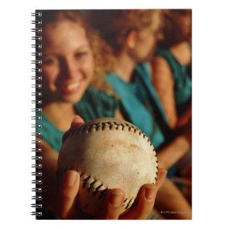 Teenage girls' softball team sitting in dugout spiral notebook