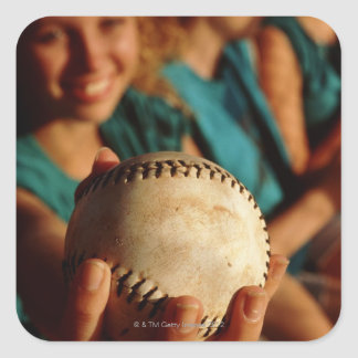 Teenage girls' softball team sitting in dugout square sticker