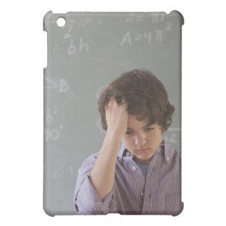 Teenaged boy in front of blackboard with math iPad mini case