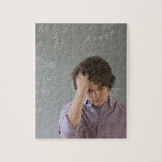 Teenaged boy in front of blackboard with math jigsaw puzzle