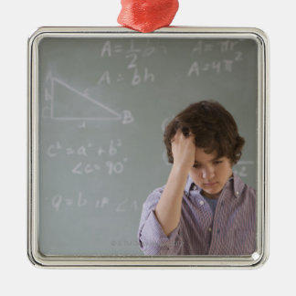 Teenaged boy in front of blackboard with math Silver-Colored square decoration