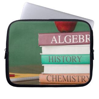 Textbooks and an apple laptop sleeve
