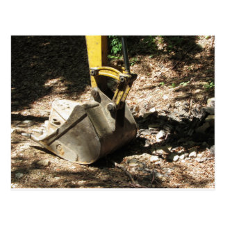 The bucket of the excavator sits at rest postcard