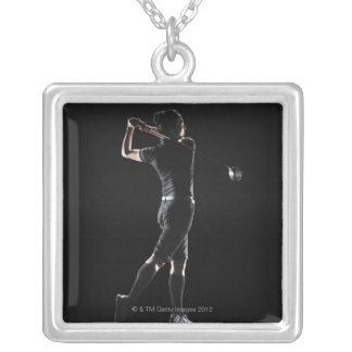 The lady golfer swings the driver of golf silver plated necklace