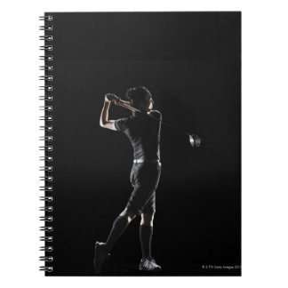 The lady golfer swings the driver of golf spiral notebook