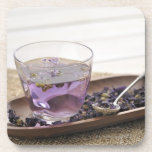 The mallow herb tea which a glass cup contains, drink coasters