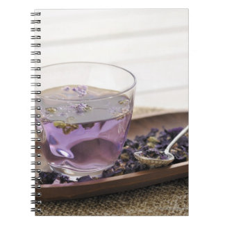 The mallow herb tea which a glass cup contains, spiral note book