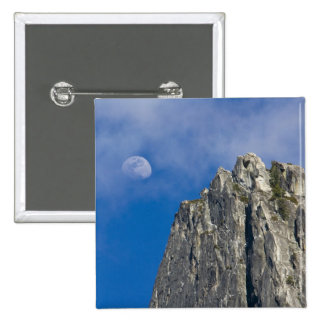 The moon rises and shines through the clouds pinback button