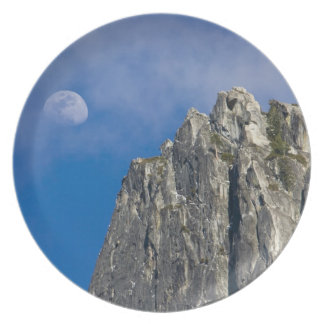 The moon rises and shines through the clouds party plates