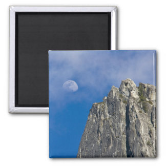 The moon rises and shines through the clouds square magnet