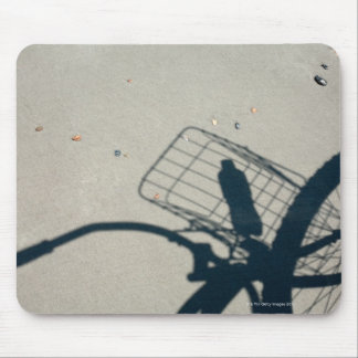 The shadow of a bicycle with a bottle of water mouse pad